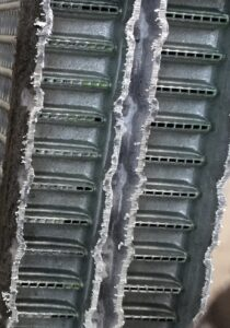 Late model evaporator cutaway revealing a manufacturing fault with a large number of galleries being blocked by solder during construction